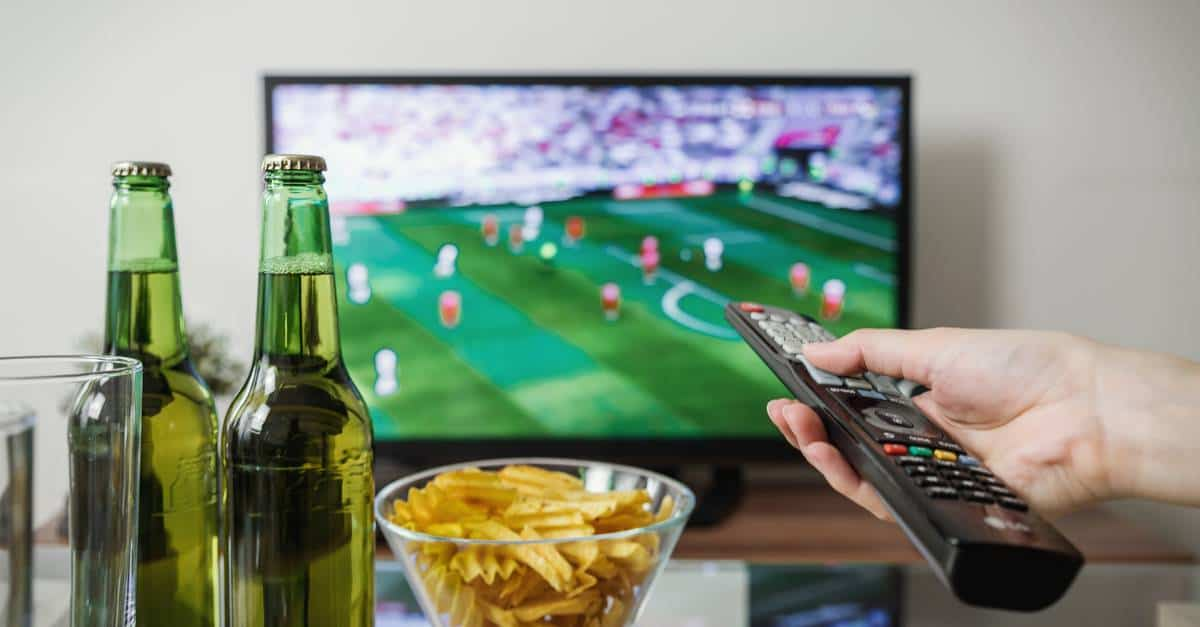 A hand holding a bottle and a television
