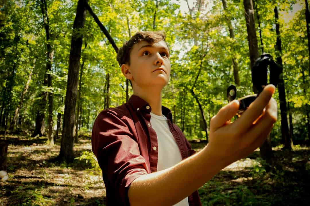 A person holding a camera in front of a forest